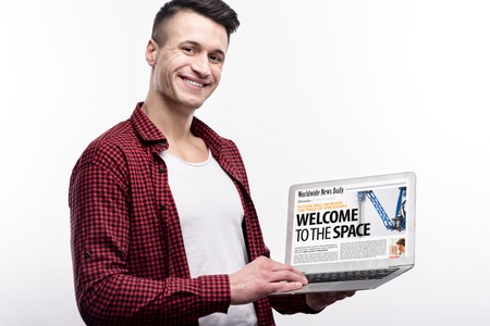 Being all-rounder. Handsome pleasant young man in a checked shirt showing a laptop with a news website tab being opened on it while posing