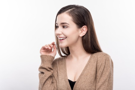 Adorable young woman laughing cutely and looking away from camera, raising one hand as if being about to cover her mouth Stock Photo
