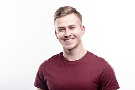 Beautiful man. The portrait of a charming fair-haired young man in a burgundy t-shirt smiling at the camera while posing isolated on a white background 版權商用圖片