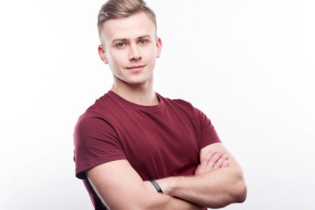Defensive position. The portrait of a well-built fair-haired young man in a burgundy t-shirt posing for the camera while folding his arms across his chest