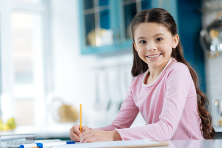 Inspired. Pretty cheerful dark-eyed dark-haired girl smiling and writing in her notebook while sitting at the computer