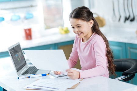 I love studying. Beautiful inspired dark-haired girl smiling and writing in her notebook while sitting at the computer and holding a sheet of paper