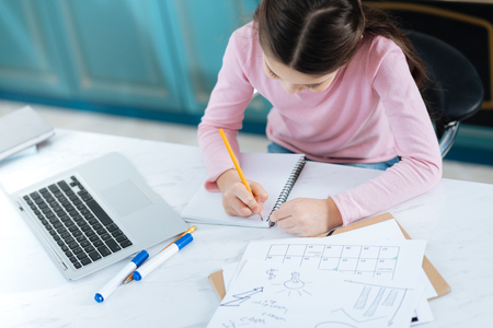 Studying hard. Determined dark-haired little girl writing in her notebook while sitting at the computer and having papers on her table Stock Photo