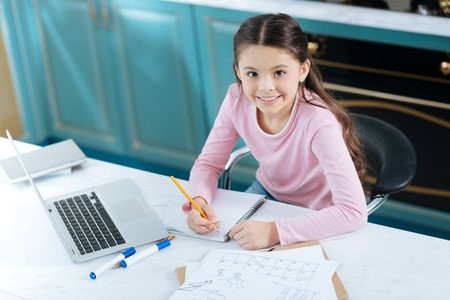 I love school. Pretty content dark-haired little girl writing in her notebook and smiling while sitting at the computer and having papers on her table Stock Photo - 94463827