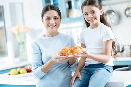 Happiness. Good-looking exuberant dark-haired little girl and her mother smiling and holding a plate with some croissants while the girl sitting on the table