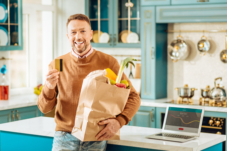 Online shopping. Nice positive happy man holding a bag with food and showing you a credit card while buying it online