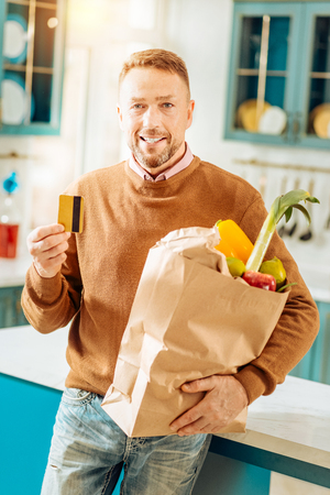 Online payment. Positive nice happy man smiling and holding his credit card while buying food online