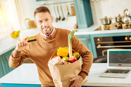 Buying food. Nice pleasant bearded man showing his credit card and looking at you while holding a bag with food