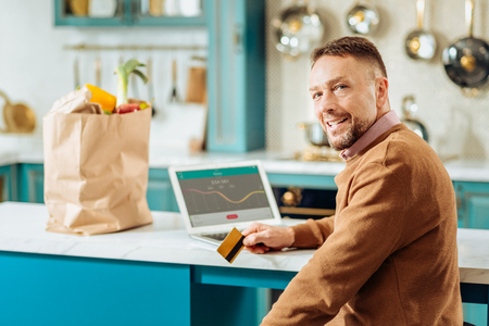 Non cash transaction. Joyful positive self employed man sitting in front of the laptop and using his credit card while making a non cash transaction Stock Photo