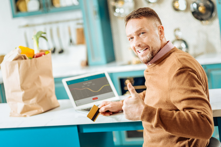 Absolutely safe. Happy nice smart man holding a credit card and showing thumbs up gesture while using online banking system