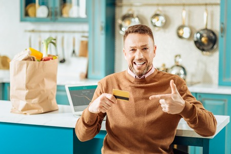 Money transaction. Happy nice positive man smiling and pointing at the credit cars while using online banking