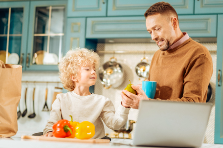 Healthy food. Positive nice handsome man standing in the kitchen and talking to his son while taking a pear from his hands