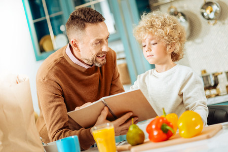Ready to cook. Pleasant nice joyful man holding a notebook and talking to his son while deciding what to cook
