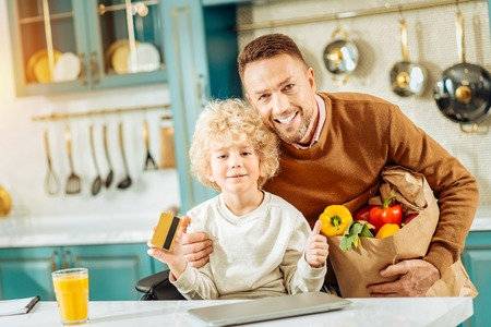 Happy parenthood. Delighted nice positive man holding a bag of food and smiling while hugging his son