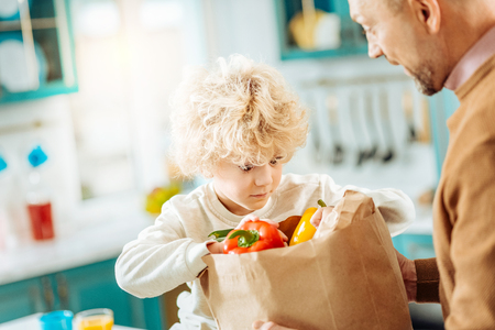 So curious. Cute curly nice boy sitting near his father and looking into the bag while being curious what is in it