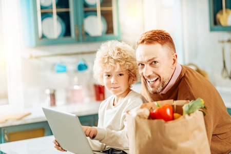 Digital device. Positive small nice boy looking at you and pointing at the laptop screen while sitting together with his father