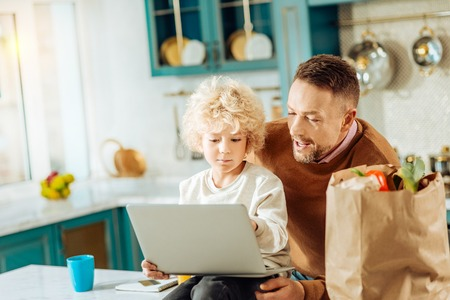 Young generation. Cute smart curly boy sitting together with his father and holding a laptop while looking at its screen