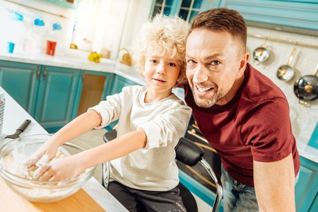 Delicious bakery. Joyful delighted young boy putting his hands in the dough and mixing it while cooking together with his father Stock Photo