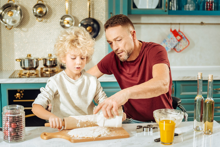 In the kitchen. Handsome positive pleasant man sitting together with his son and holding a jar with flour while helping him in the kitchen
