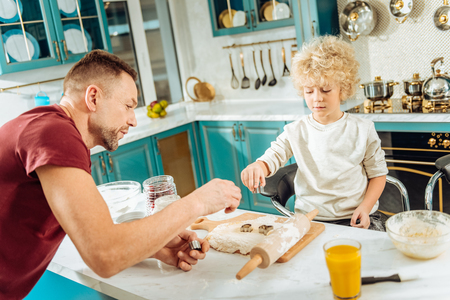 Beautiful cookies. Pleasant nice smart boy standing opposite his father and using cookie molds while baking together with him Stock Photo