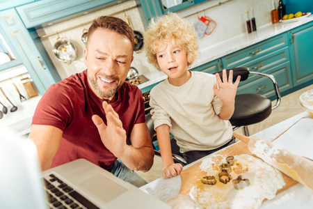 Say hello. Joyful nice positive man holding a laptop and waving his hand while standing in the kitchen together with his son