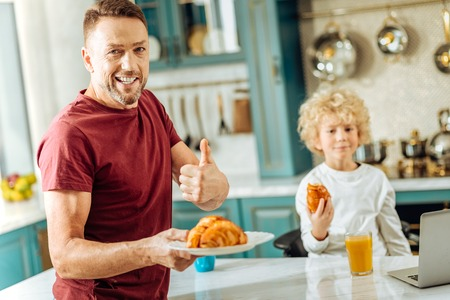 Good job. Happy positive delighted man standing in the kitchen and looking at you while holding a plate with croissants