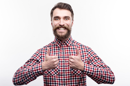 Pleased by results. Happy bearded young man in a checked shirt showing thumbs up and grinning while posing isolated on a white background Stock Photo