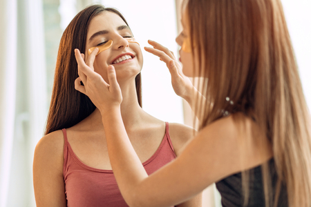 Sisterly care. Pleasant teenage girl helping her elder sister apply under-eye patches, adjusting them properly on her skin while the other girl smiles Stock Photo