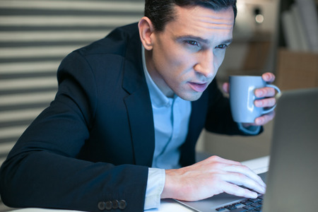 Computer error. Serious ambitious pretty businessman carrying cup while working on laptop and staring at the screen