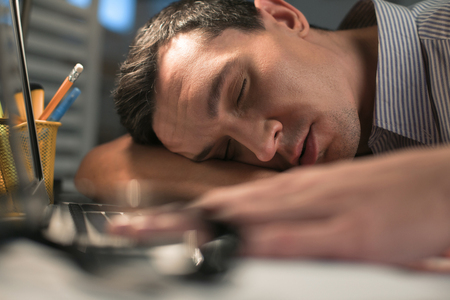 Sleep on table. Handsome peaceful male employee spending night at office while sleeping on the table and placing head on hand