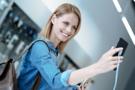 Time for selfie. Beautiful female person having backpack and keeping smile on her face while testing modern smartphone