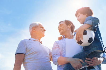 Men day. Low angle shot of a cheerful father holding his adorable son in arms while enjoying a pleasant conversation with his day after playing football in a family circle.