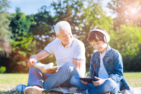 Only men day. Positive minded senior man with a book looking at his smiling preteen grandson while the boy listening to music and enjoying the day spent together with his granddad.