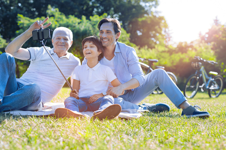 Peace and harmony. Friendly family members spending their day outdoors and smiling cheerfully while posing and taking a selfie together. Stockfoto
