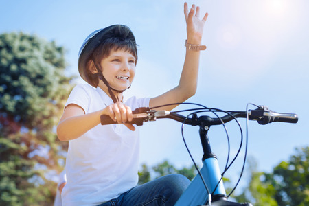 Oh hello there. Low angle shot of a charming kid grinning broadly while holding his bicycle and lifting his arm to welcome somebody outdoors. Stok Fotoğraf