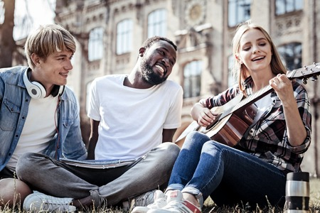 Real talent. Happy positive joyful men sitting on the grass and smiling while listening to the song of their friend Stock Photo
