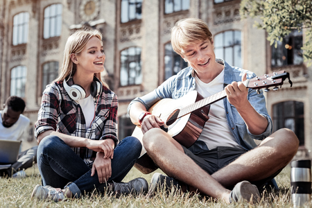 Beautiful song. Delighted happy young man holding a guitar and playing music while spending time with his friend outdoors