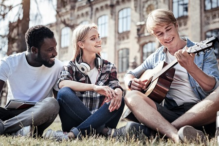 Musical instrument. Delighted nice positive man sitting on the grass and looking at his guitar while playing music to his friends