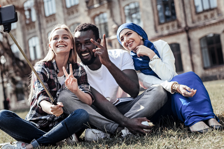 Great mood. Cheerful positive emotional student showing V sign and looking into the smartphone camera while taking a selfie together Stok Fotoğraf