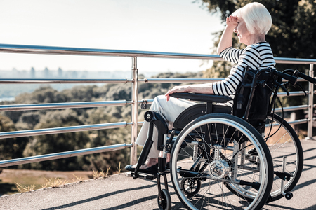 Beautiful landscape. Nice pleasant elderly woman sitting in the wheelchair and looking at the view while covering her eyes from sun