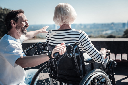 Amazing view. Happy positive cheerful man smiling to an elderly woman and pointing with his hand while showing her the view Stock Photo