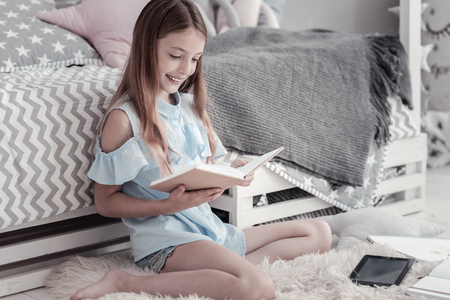 Avid reader. Good-looking cheerful smiling girl wearing a blue dress and holding a book while sitting on the floor with her tablet and notebooks near her and a bed in the background