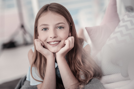 Leisure time. Pretty vigorous long-haired grey-eyed girl smiling and relaxing while lying on bed Stock Photo