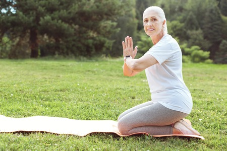 Yoga practice. Positive pleasant aged woman sitting on a yoga amt and looking at you while holding her hands together