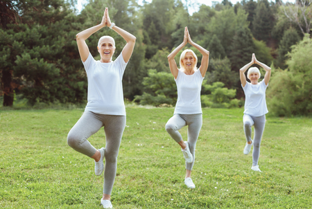 Keeping balance. Joyful positive aged women standing in the part and holding their hands up while practicing yoga Stock Photo
