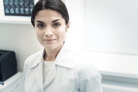 Experienced neurologist. Portrait of a professional skillful female doctor smiling and looking at you while working as a neurologist in the hospital
