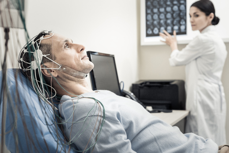 Electro scanning. Nice pleasant handsome man lying on the medical bed and wearing electronic wires while having his brain scanned Stock fotó