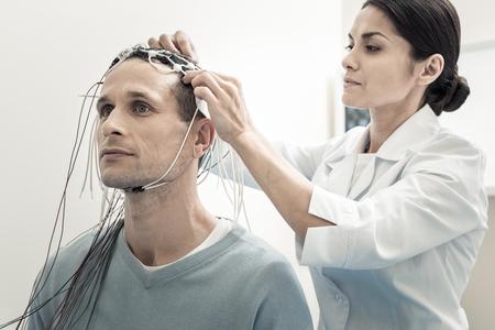 Escaneo cerebral. Doctora seria profesional de pie detrás de su paciente y ronroneando electrodos en su cabeza mientras lo prepara para el electroencefalograma Foto de archivo