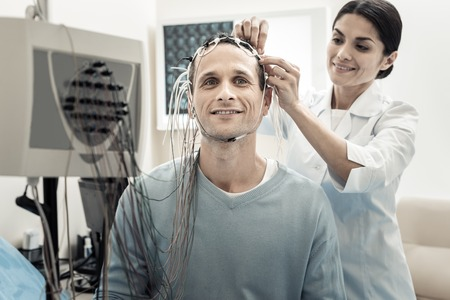 Medical diagnostics. Cheerful happy handsome man wearing electrodes and smiling while being ready for diagnostics