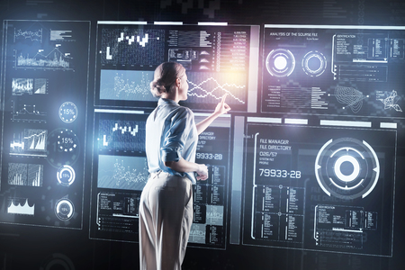 Necessary changes. Clever experienced concentrated young employee standing in front of a big futuristic screen and touching it while doing necessary changes in the program